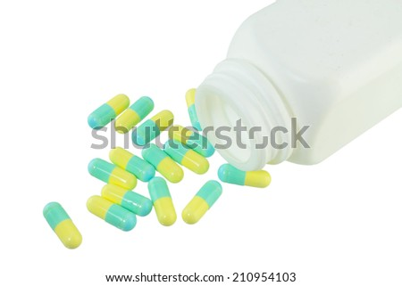 Pills Capsule, Herb capsule spilling out of a bottle on white background.