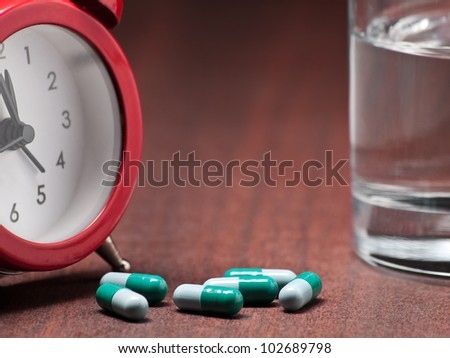 Pills , clock and glass of water on the night table,closeup, for healthcare,medicine,drug themes - stock photo