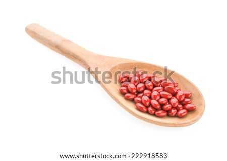 Pills drug on wooden spoon isolated on white background