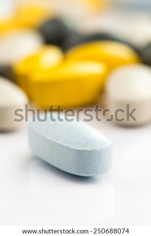 Pills in different vibrant colors. Blue one is in front of the photograph and in focus.