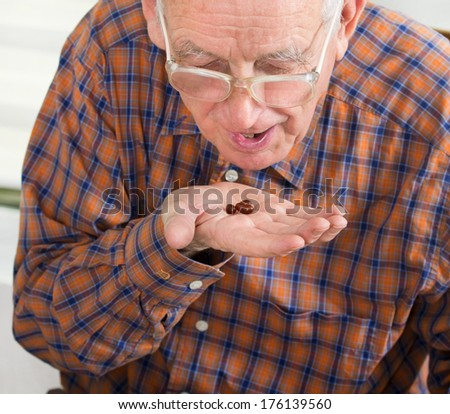 Pills in old man's hand close to mouth ready to take them - stock photo