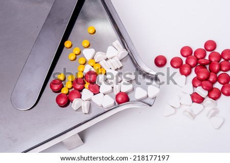 pills in pill counting tray,Red tablets medicine on the drug count tray,Yellow tablets medicine on the drug count tray ,White tablets medicine on the drug count tray