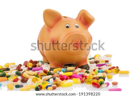 pills lying next to a piggy bank. symbolic photo for costs in medicine and pharmaceutical industry - stock photo