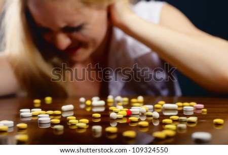 Pills lying on the table before suffering from the pain the young woman - stock photo
