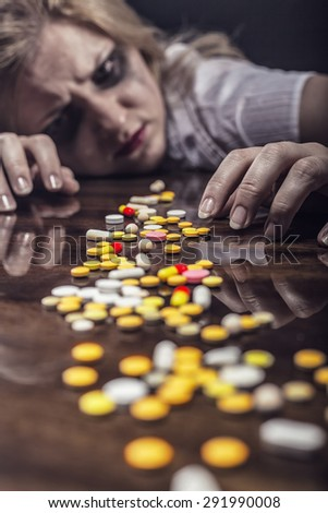 Pills lying on the table before suffering from the pain the young woman. Focus on pills - stock photo