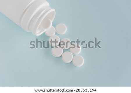pills medicine and pills bottles on light blue background - stock photo