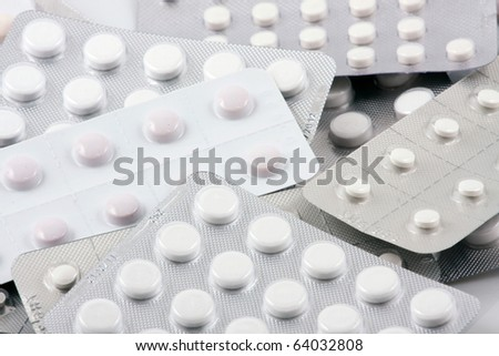 Pills of many shapes and colors grouped together