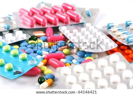Pills of many shapes and colors grouped together - stock photo