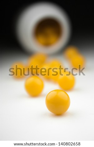 Pills of vitamin C close-up spilled out open container. - stock photo