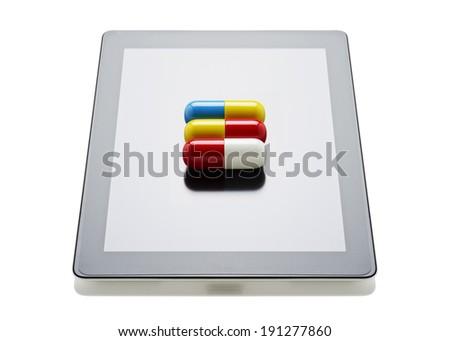 Pills on a digital tablet  - stock photo