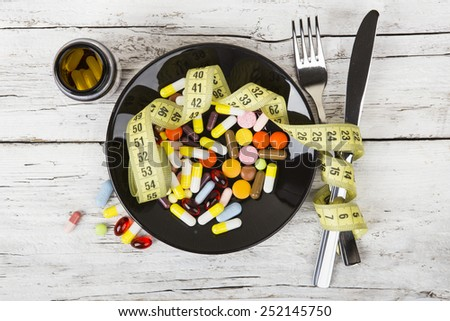 pills on a plate with a measuring tape - stock photo