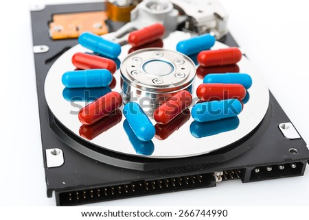 Pills on computer hard drive - concept technology background - stock photo