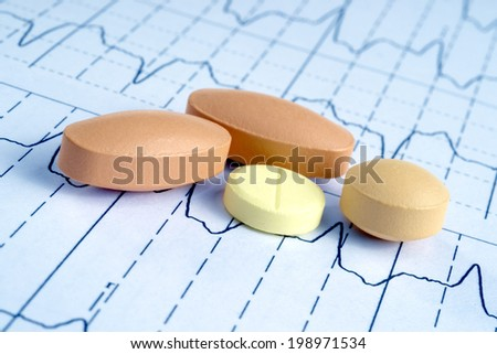 pills on the cardiogram background - stock photo
