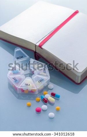 Pills planner with weekly medication capsules in it and note book - stock photo