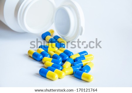 Pills pouring from white pill bottle