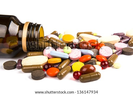 Pills pouring out of the brown bottle - stock photo
