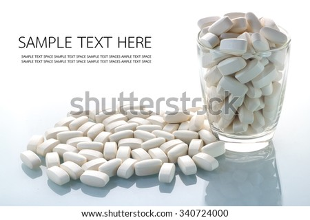 Pills pouring out of the glass with white background