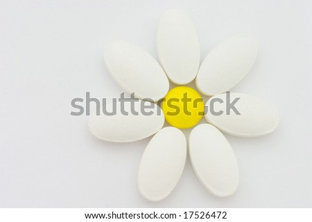 Pills, putted together in form of camomile flower. Symbol of nature, health and herbal medicines.
