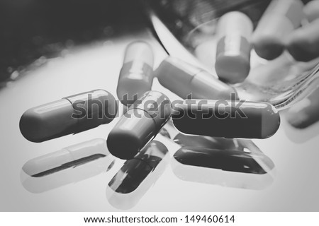 Pills scappered on a glass surface. Black and white style. - stock photo