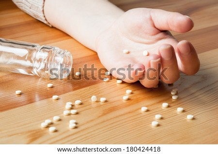 Pills spilled out of suicide hand - stock photo