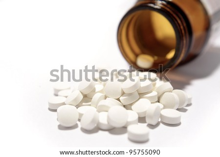 Pills spilling from container on plain background - stock photo
