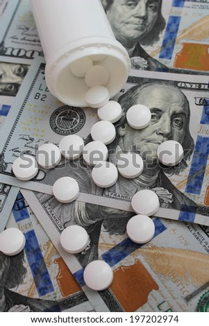 Pills spilling from container  on the background of dollars  - stock photo