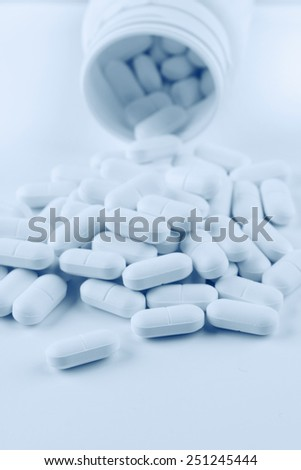 Pills spilling from plastic container - stock photo