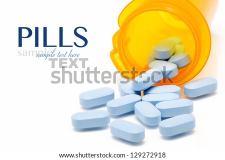 Pills spilling out of a pill bottle isolated on white with sample text - stock photo