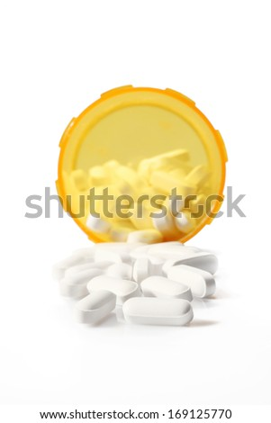 pills spilling out of a prescription bottle with a safety cap - stock photo