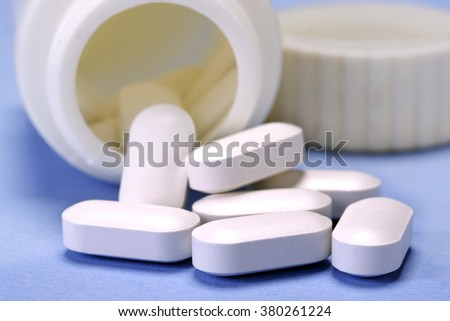 Pills spilling out of bottle - stock photo