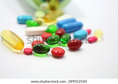 Pills spilling out of pill bottle - stock photo