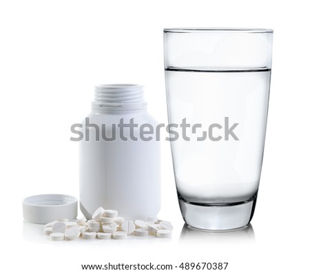 Pills spilling out of pill bottle and Glass of water
