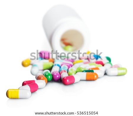 Pills spilling out of pill bottle on white background