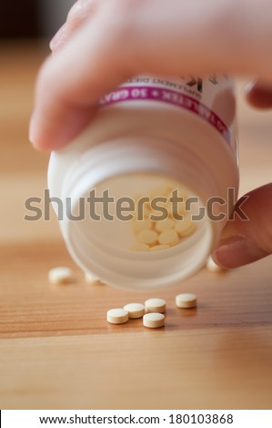 Pills spilling out of white pill bottle - stock photo