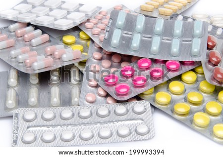 Pills, tablets and capsules in blister packs, isolated on white - stock photo