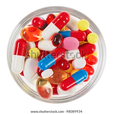 Pills, tablets and drugs heap in glass bowl isolated on white - stock photo