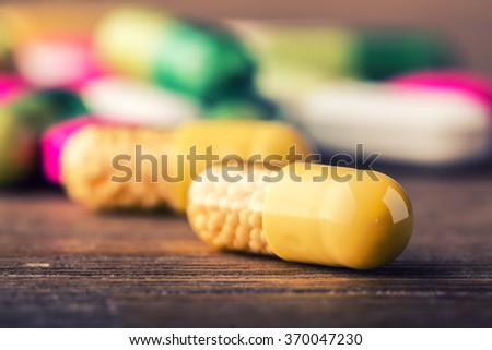 Pills. Tablets. Capsule. Heap of pills. Medical background. Close-up of pile of yellow pink green tablets - capsule. Pills and tablets. - stock photo