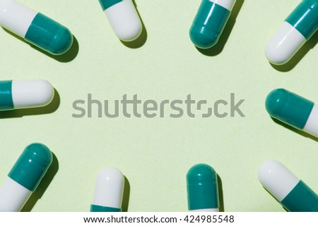 Pills. Tablets. Capsule. Top view of pile of yellow green tablets - capsule. Pills and tablets. Green background. Medical background.  - stock photo