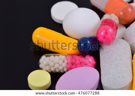 Pills, tablets, capsules isolated on a black background