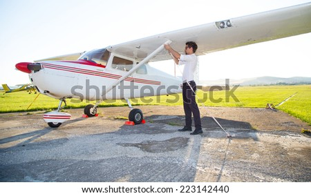 Pilot anchoring plane with cord - stock photo