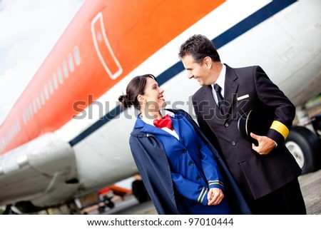 Pilot and flight attendant at the airport with an airplane at the background - stock photo