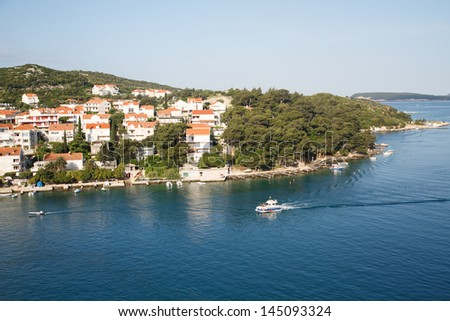 Pilot boat cruising past coastal homes on the coast of Croatia in Dubrovnik