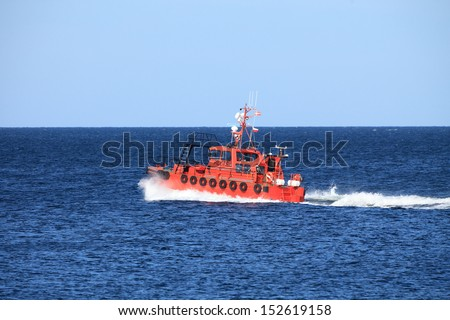 pilot boat orange tugboat at the sea monitors ships. Coastal safety, salvage and rescue  - stock photo