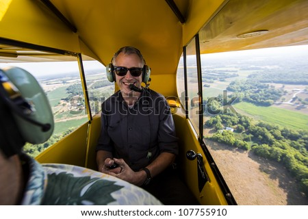 Pilot flying small aircraft with farm land in background - stock photo