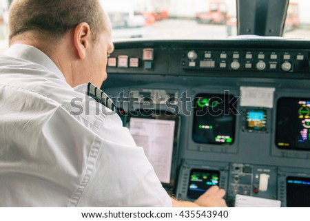 Pilot in an aircraft cockpit preparing for the flight.