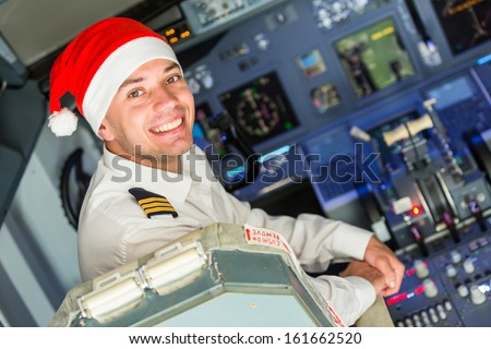 Pilot in the Cockpit with Santa Hat - stock photo