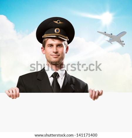 pilot in the form of holding an empty billboard on the background of sky and flying plane, place for text - stock photo