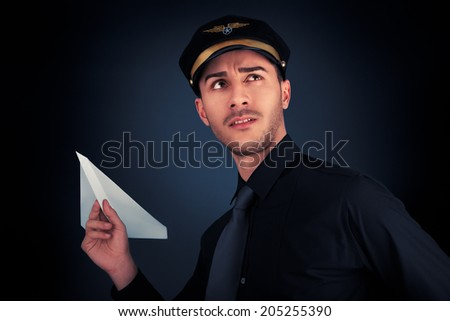 Pilot Launching Paper Airplane - Young pilot wearing black shirt and tie launches a paper airplane   - stock photo
