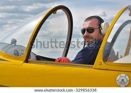 Pilot of a small aerobatic plane having rest in the cockpit after a flight