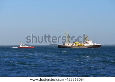 Pilot ship leading cargo ship to port - stock photo